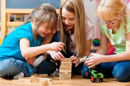 children playing with toys: Children - sisters - playing at home with bricks Stock Photo