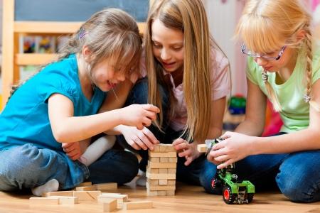 juguetes: Ni�os - hermanas - jugando en su casa con ladrillos