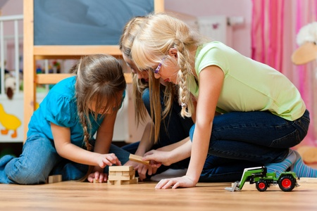 board game: Children - sisters - playing at home with bricks Stock Photo