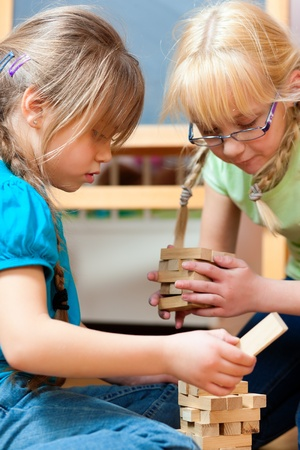 sibling: Children - sisters - playing at home with bricks Stock Photo