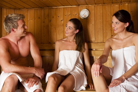 three people: Three people (one male, two female) enjoying a hot sauna, having a casual chat