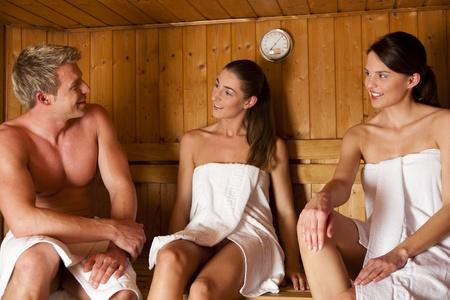 three women: Three people (one male, two female) enjoying a hot sauna, having a casual chat