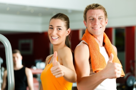 health clubs: Sportive couple in gym or fitness club looking at the viewer