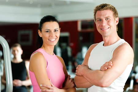 exercise man: Sportive couple in gym or fitness club looking at the viewer
