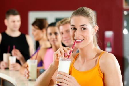 белки: Люди питьевой протеиновый коктейль после тренировки в тренажерном зале или фитнес-клубе Фото со стока