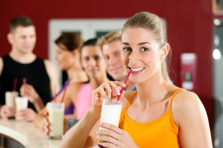 People drinking protein shake after workout in gym or fitness club photo