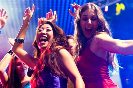 Groep van de partij van mensen - mannen en vrouwen - dansen in een discotheek aan de muziek