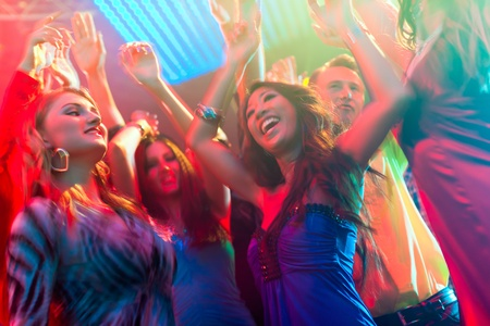night club: Group of party people - men and women - dancing in a disco club to the music