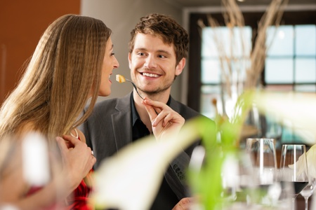 Couple for romantic Dinner or lunch in a gourmet restaurant, he is feeding her Stock Photo - 10016499