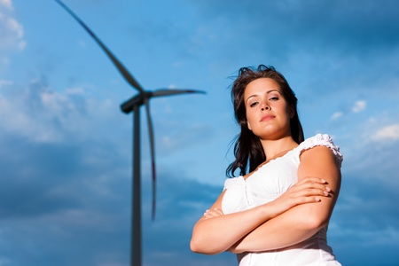 Young woman standing in front of windmill and the blue sky Stock Photo - 10016603