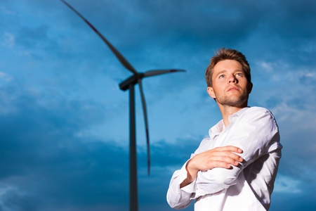 conservationist: Young man standing in front of windmill and the blue sky