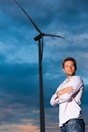 Young man standing in front of windmill and the blue sky Stock Photo - 10021158