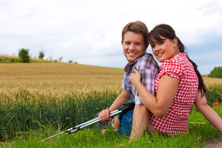 Young fitness couple doing sports outdoors; making a break from hiking in summer Stock Photo - 10021632