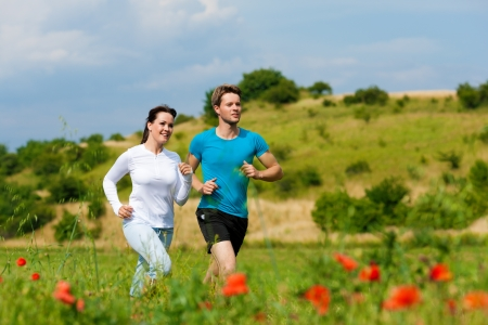 Young fitness couple doing sports outdoors; jogging on a green meadow in summer under the sky with lots of clouds Stock Photo - 10021016