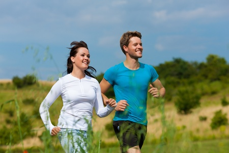 men exercising: Young fitness couple doing sports outdoors; jogging on a green meadow in summer under the sky with lots of clouds Stock Photo