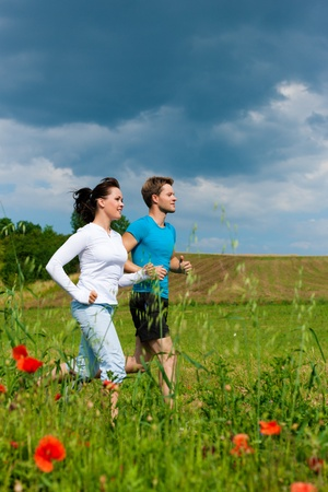 Young fitness couple doing sports outdoors; jogging on a green meadow in summer under the sky with lots of clouds photo