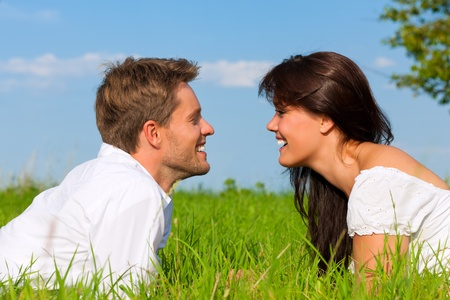 Happy couple lying on a meadow in summer looking at each other in love