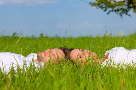 Happy couple lying on a meadow in summer dreaming about their shared future Stock Photo