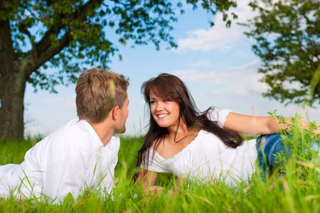 enamoured: Happy couple lying on a meadow in summer Stock Photo