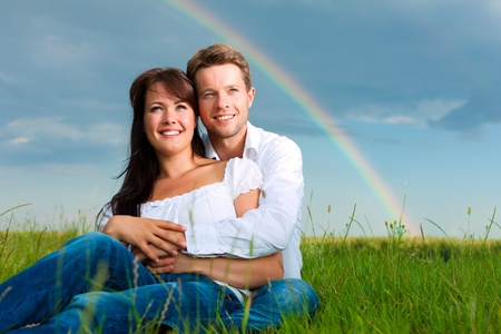 Happy couple caught in a daydream sitting on a meadow in summer; in the background a rainbow photo