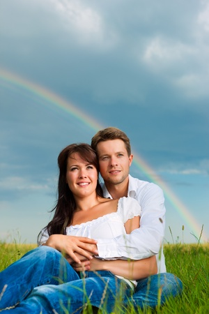 daydream: Happy couple caught in a daydream sitting on a meadow in summer; in the background a rainbow
