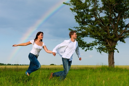 Happy couple running on a meadow in summer; in the background a rainbow photo