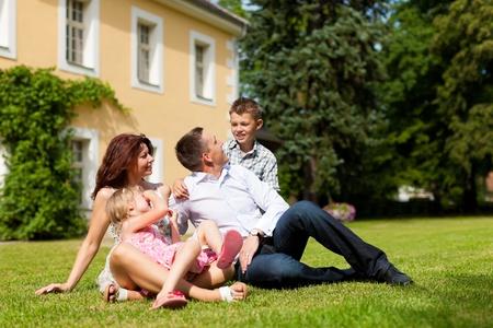 Junge gl�ckliche Familie sitzen in der Sonne auf dem Rasen vor ihrem neuen Zuhause - eine Villa