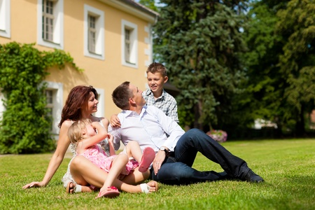 Young happy family sitting in the sun on the lawn in front of their new home - a villa
