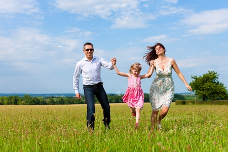 Happy family - mother, father, child - running over a green meadow in summer Stock Photo