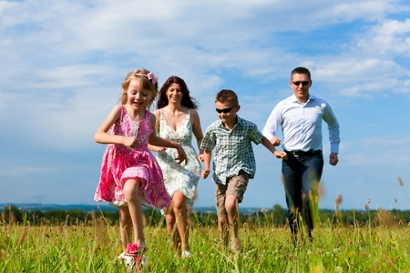 father children: Happy family - mother, father, children - running over a green meadow in summer kicking a soccer ball   Stock Photo