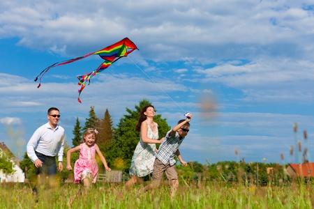Gelukkige familie - moeder, vader, kinderen - lopen over een groene weide in de zomer; ze vliegen een vlieger