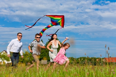 active family: Happy family - mother, father, children - running over a green meadow in summer; they fly a kite