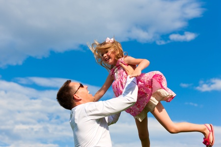 affairs: Family affairs - father and daughter playing in summer; he is throwing her into the air Stock Photo