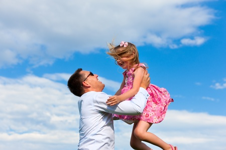 Family affairs - father and daughter playing in summer; he is throwing her into the air Stock Photo