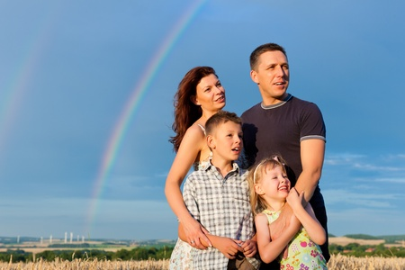 father children: Happy family - mother, father, children - standing under a Rainbow in summer looking into a glorious future