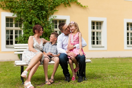 mother on bench: Young happy family sitting in the sun in front of their new home on a bench - it is a villa Stock Photo