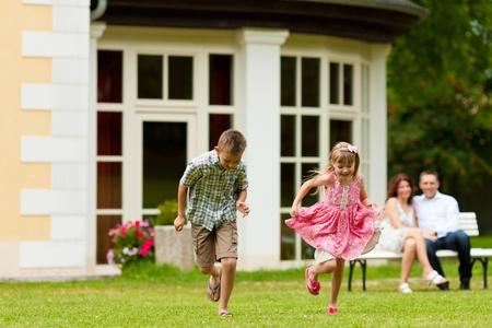 Junge gl�ckliche Familie - die Kinder spielen und die Eltern in der Sonne sitzen auf einer Bank vor ihrem Haus