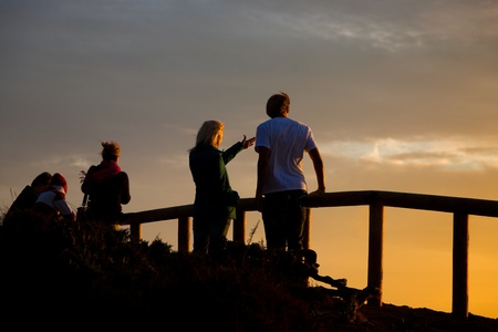 balustrade:  Young couple standing on balustrade on cliff line in front of the ocean and watching the sunset