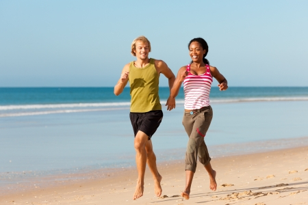 couple exercising: Young sport couple - Caucasian man and African-American woman - jogging on the beach