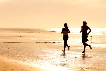 가벼운 흔들림: 젊은 스포츠 몇 - 선셋에서 해변에서 조깅