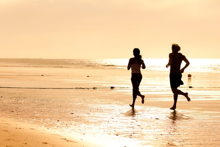 woman jogging: Young sport couple - jogging on the beach in sunset