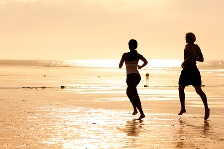Young sport couple - jogging on the beach in sunset Stock Photo - 10020650