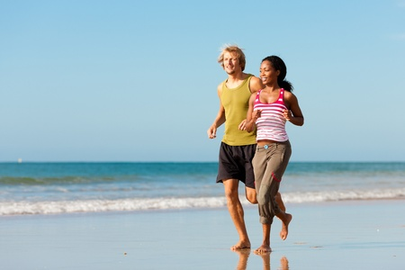 healthy exercise: Young sport couple - Caucasian man and African-American woman - jogging on the beach