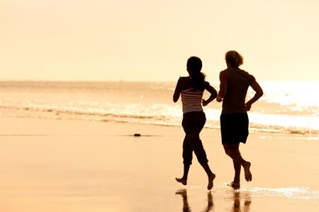 hombres haciendo ejercicio: Pareja joven deporte - jogging en la playa en sunset   Foto de archivo