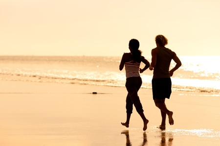 men exercising: Young sport couple - jogging on the beach in sunset