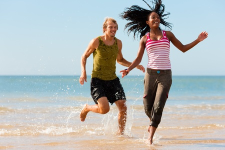Young sport couple - Caucasian man and African-American woman - jogging on the beach in a playful mode photo