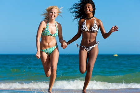 Friends - two women - on the beach having lots of fun in their vacation running through the water photo
