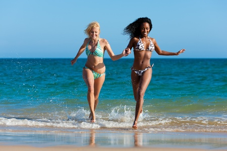 kadınlar: Friends - two women - on the beach having lots of fun in their vacation running through the water Stok Fotoğraf