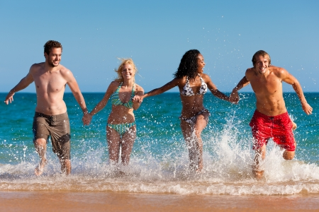 Four friends - men and women - on the beach having lots of fun in their vacation running through the water photo