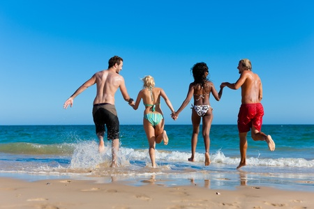four friends: Four friends - men and women - on the beach having lots of fun in their vacation running through the water